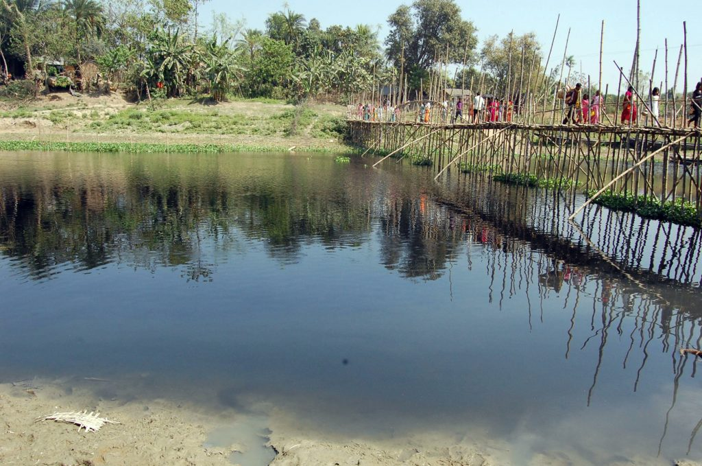 Villagers crossing the polluted Churni river course in Majhdia using a bamboo bridge. Picture by PRANAB DEBNATH