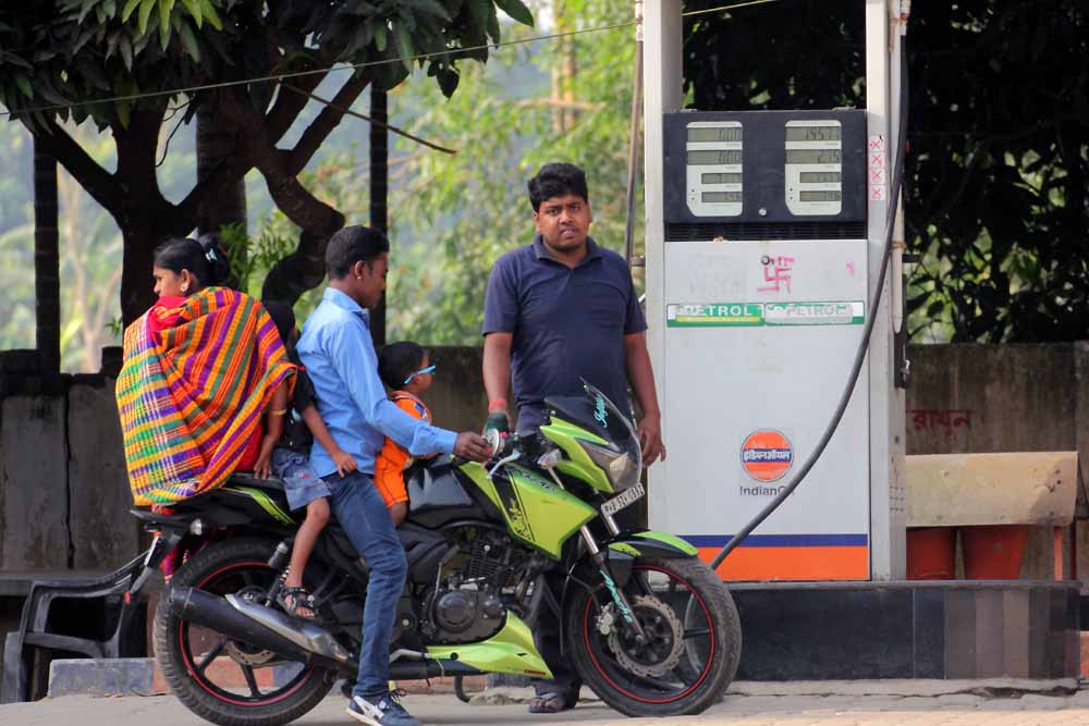 A pump worker refueling a bike with its riders appearing without helmet. Picture by Abhi Ghosh