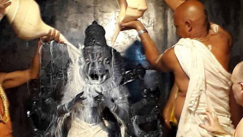 The deity of Lord Narasimha being at ISKCON given a bath on the occasion