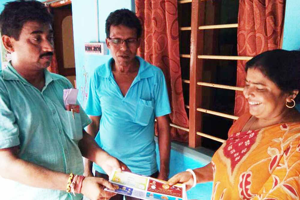 BJP workers speaking to a homemaker in Dhubulia. Picture by Pranab Debnath