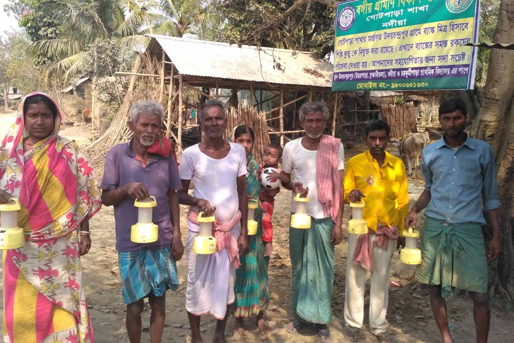 Villagers in Char Kurmipara with the nonfunctioning CFL lantern given by the Nadia administration. NfN Picture