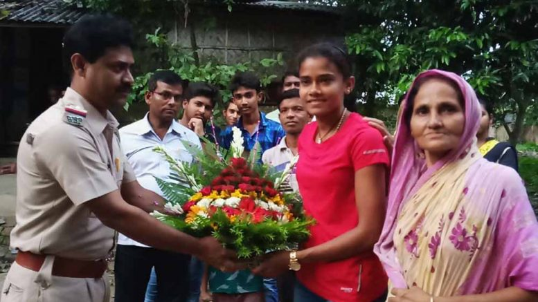 Debashree Majumder being handed over with a bouquet by a police officer