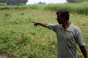 A villager showing his piece of agricultural land that would be acquired if the proposed bypass is constructed