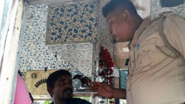 A Police official talking to a passenger in bus of Krishnanagar-Karimpur route.
