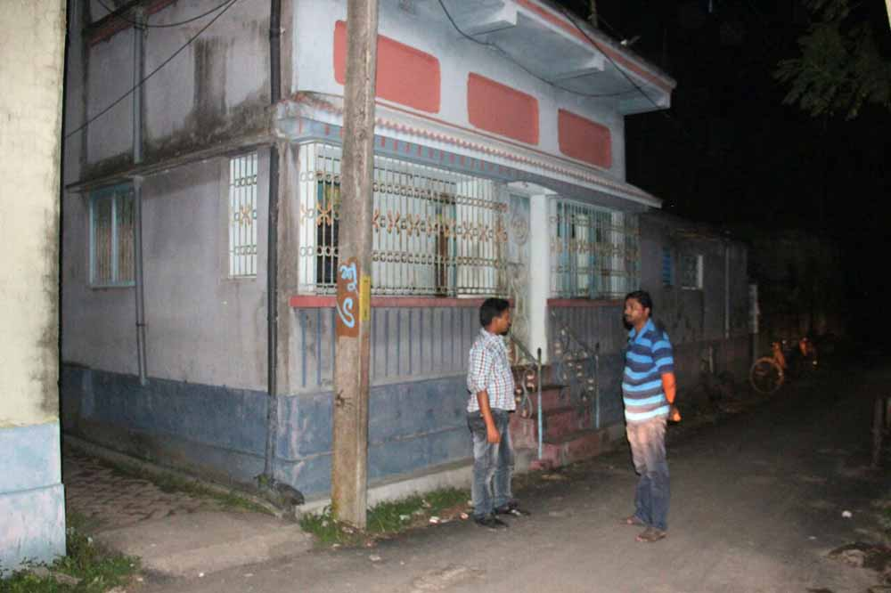 Two civic volunteers on vigil in front of house of a Trinamul councilor in Santipur