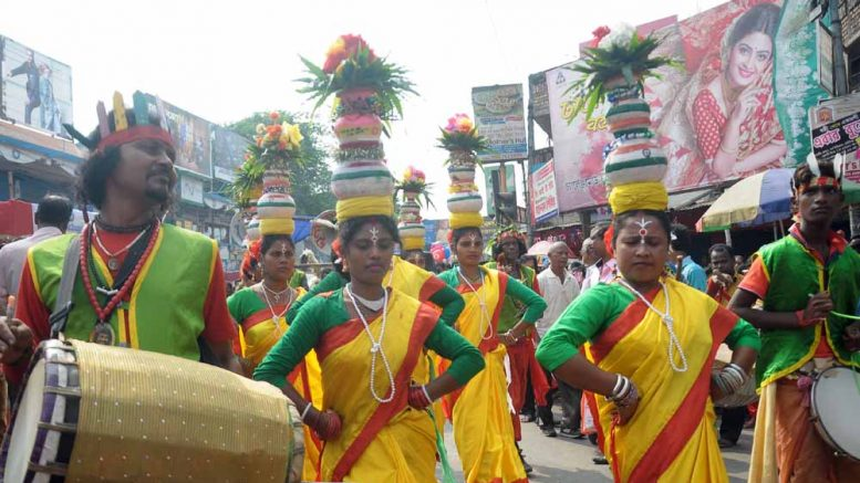 Women in colorful attire walking in procession with the Mangal Ghat in Krishnanagar on Monday morning. Picture by Pranab Debnath