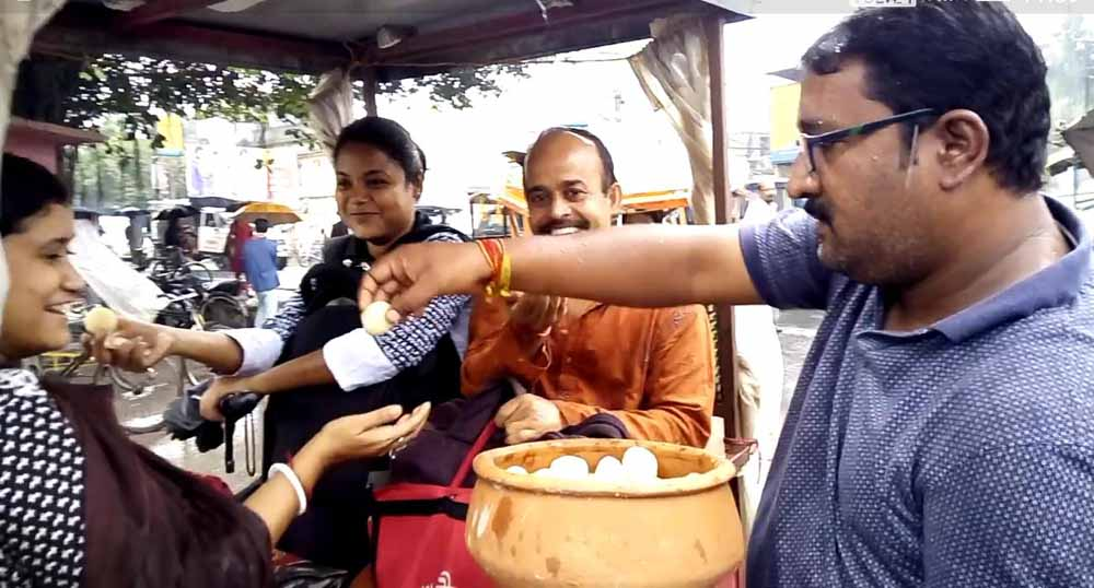 A volunteer distributing Rasogolla among some Toto riders in Ranaghat on Wednesday.