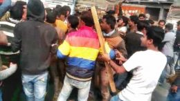 Trinamul activists with a bamboo poles in hand block the way of the BJP's motorbike rally in Plassey