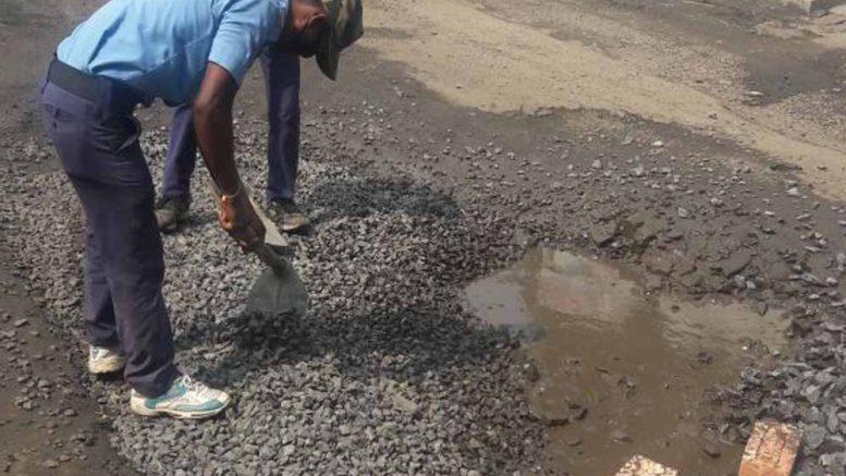 A civic volunteer repairs the road in Govindapur of Santipur