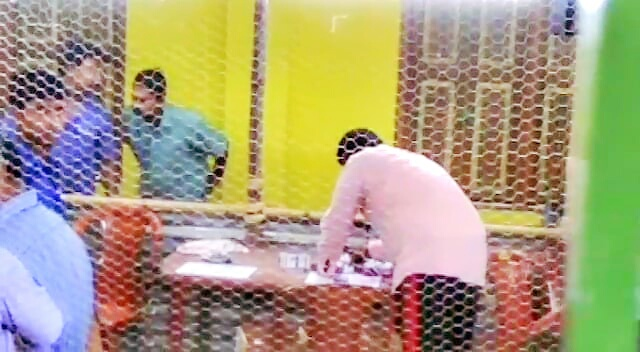 Saheb Ghosh stamping ballots inside a counting hall in Majhdia