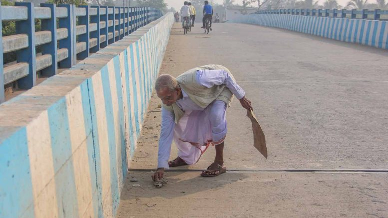 Rajkumar Pal cleaning the road over the Jugal Kishore Bridge
