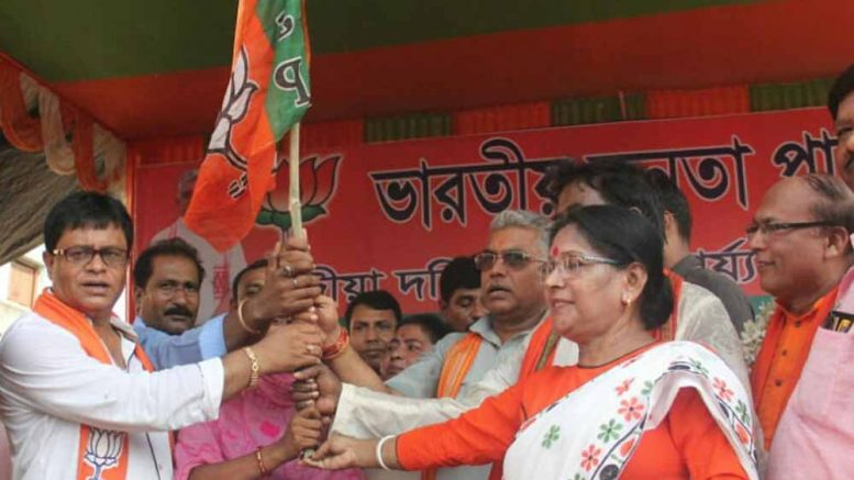 A new entrant to BJP receiving party flag from Dilip Ghosh in Ranaghat on Thursday
