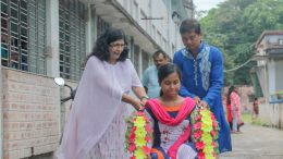 Santipur College Principal Chandrima Bhattacharjee and Non-teaching staff Biswajit Roy take a physically challenged student to classroom on wheelchair
